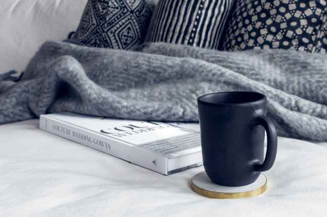 black ceramic mug on round white and beige coaster on white textile beside book
