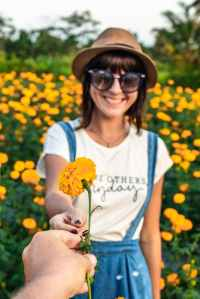 person giving flower to smiling woman